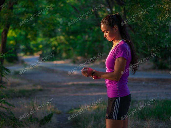 Portrait of sporty young beautiful woman in fitness wear and tracker on nature background