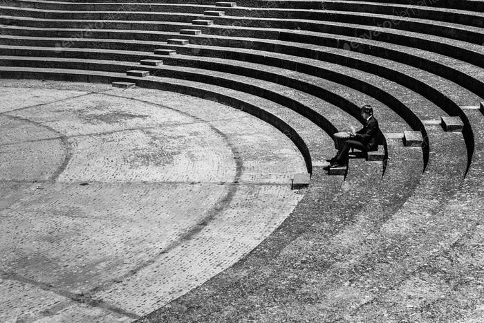 A musician playing alone his timbale in an amphitheater.