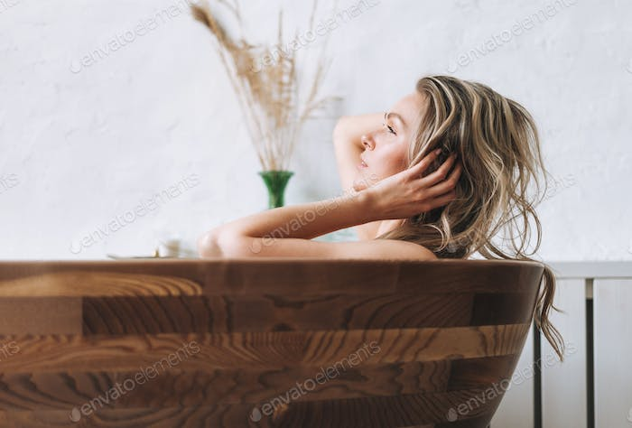 Blonde smiling woman 35 year plus with long hair takes a bath