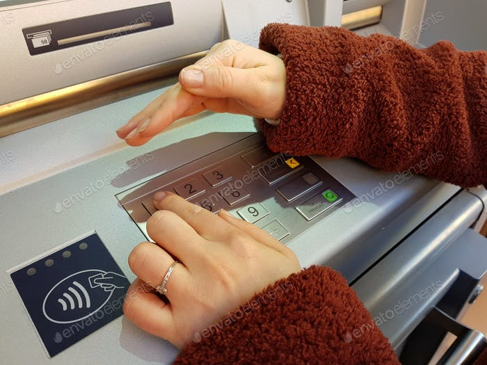 Woman typing her security pin number on an atm keypad