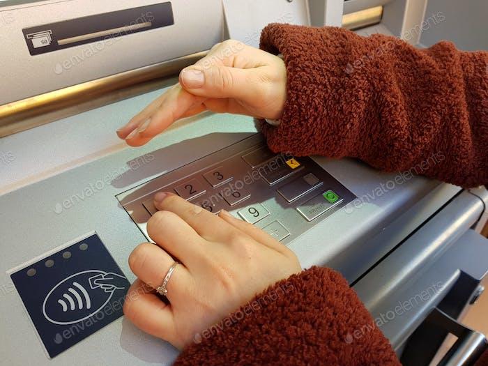 Frau, die ihre Sicherheits-Pin-Nummer auf einem ATM-Tastatur eingeben