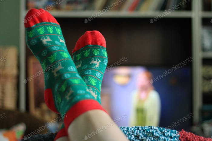 Watching television in my cozy home, socks, Christmas time, focus on foreground