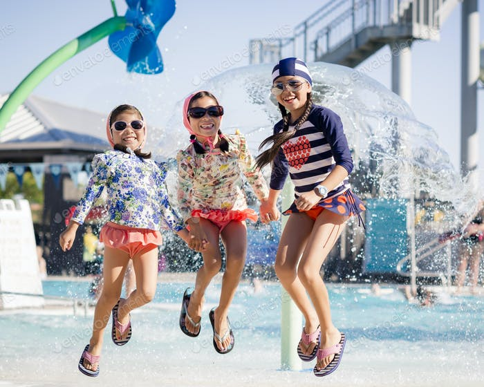 Girls jumping in front of a pool