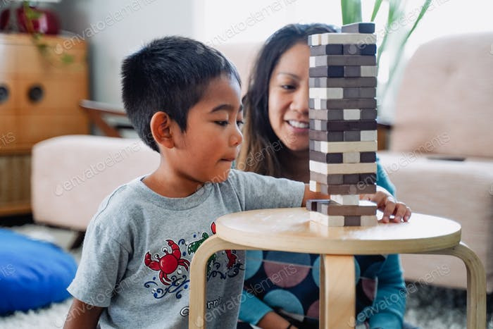 Diverse young little boy playing board game at home distance learning childhood memories unplugged s
