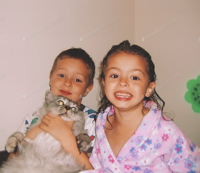 Little kids, brother and sister in theirs pajamas with a big fluffy cat ready for bedtime
