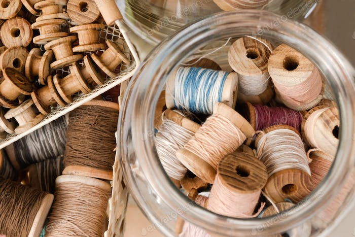 Top view on small wooden coils in a basket and big coils with colorful threads in a glass jar.