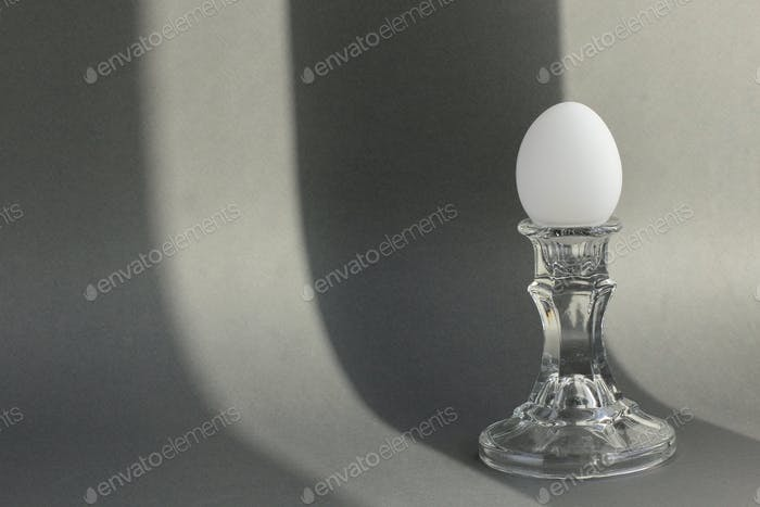 A white chicken egg in a vintage classic glass candlestick holder on a textured gray background with