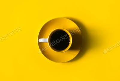 Yellow cup of coffee on yellow background