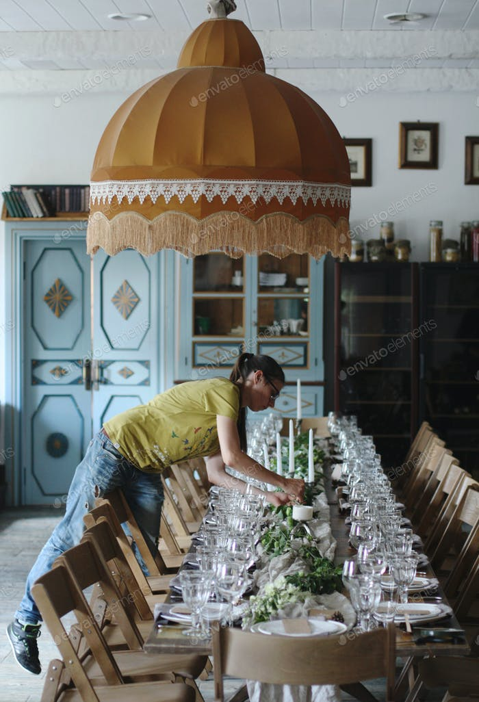 Florist makes the decoration of a festive table in a restaurant, the profession of a florist
