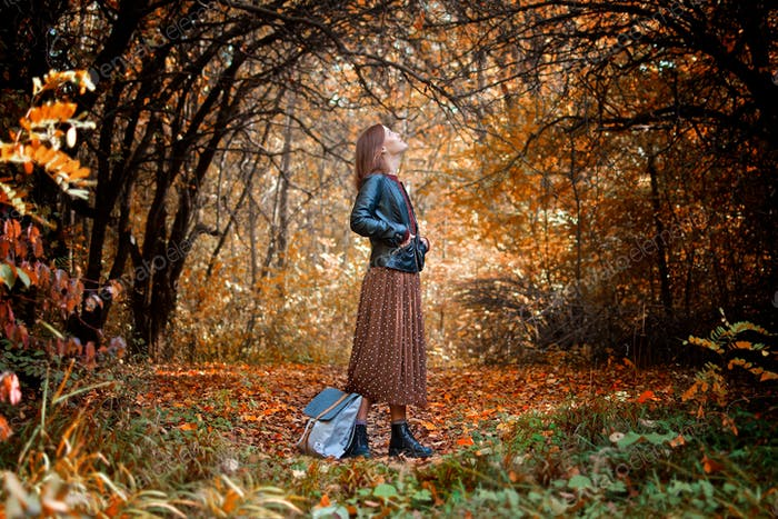 Beautiful girl standing in the autumn forest