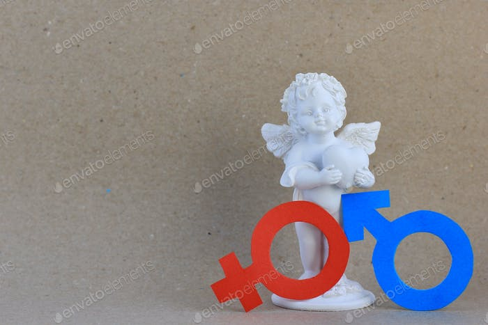 Figurine of angel with red female and blue male paper gender symbols. Valentine's day, love.