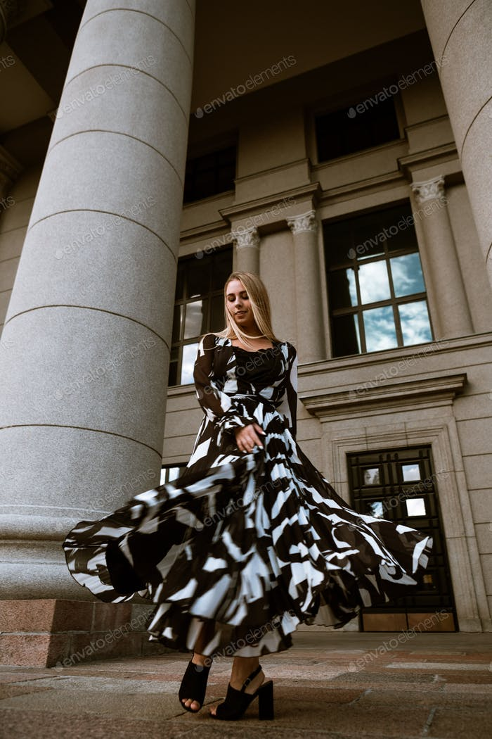 Well dressed woman playing with her dress outdoors