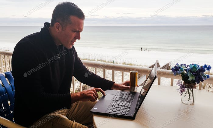 Millenial on vacation in outdoor living space working on his laptop while drinking beer and enjoying