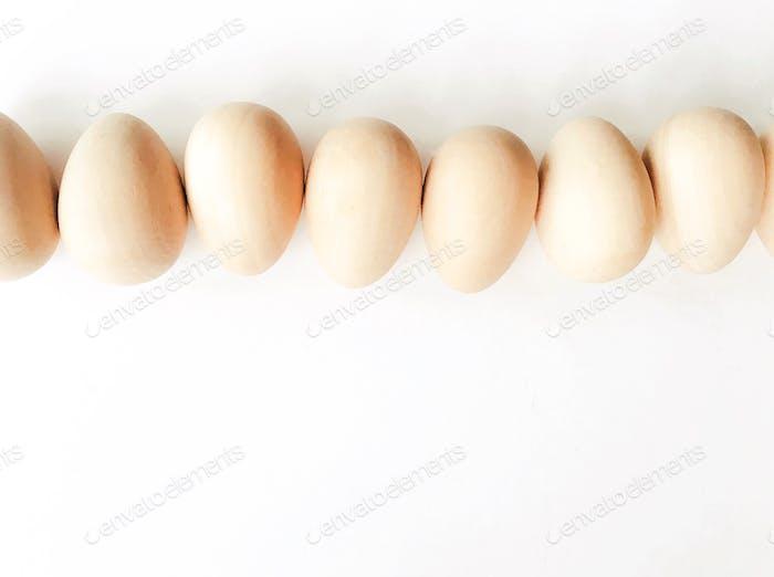 Blick nach unten auf horizontale Reihe von hölzernen Eiern auf einem weißen Hintergrund.
