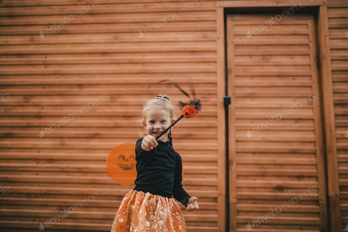 Cute girl wearing Halloween suit with pumpkin bucket with candies. Trick or treat.