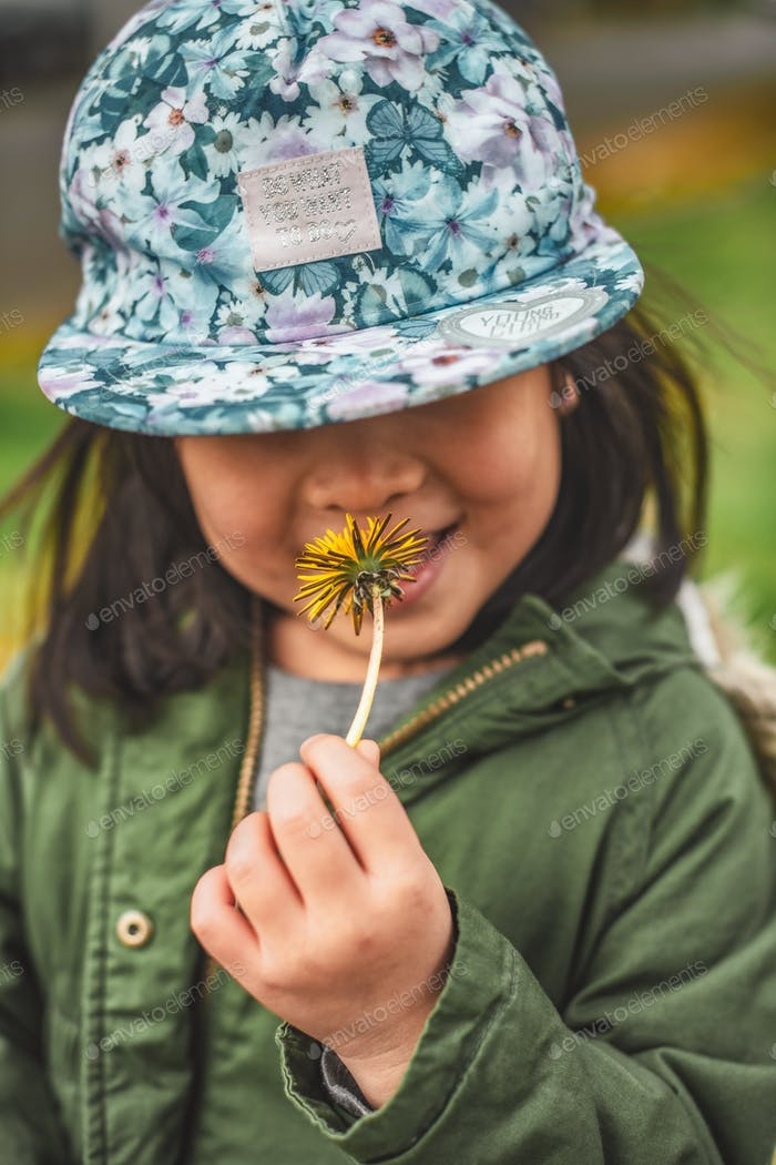 Smiley toddler girl with dandelion