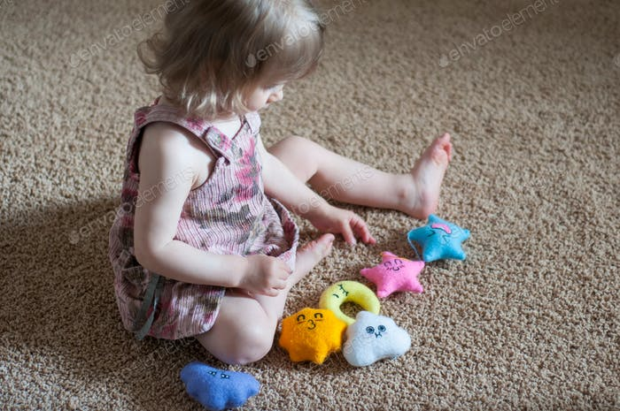 Little girl baby girl playing with handmade felt toys on the beige carpet