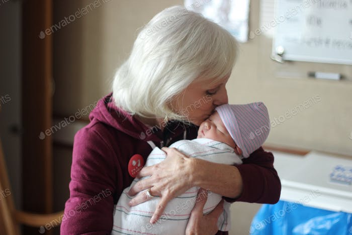 A grandmother kisses her new grandchild at the hospital.