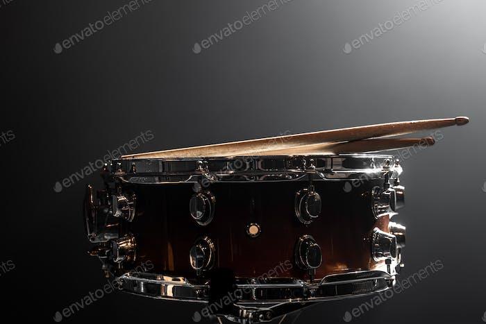 Close-up snare drum and drum sticks on a dark background.