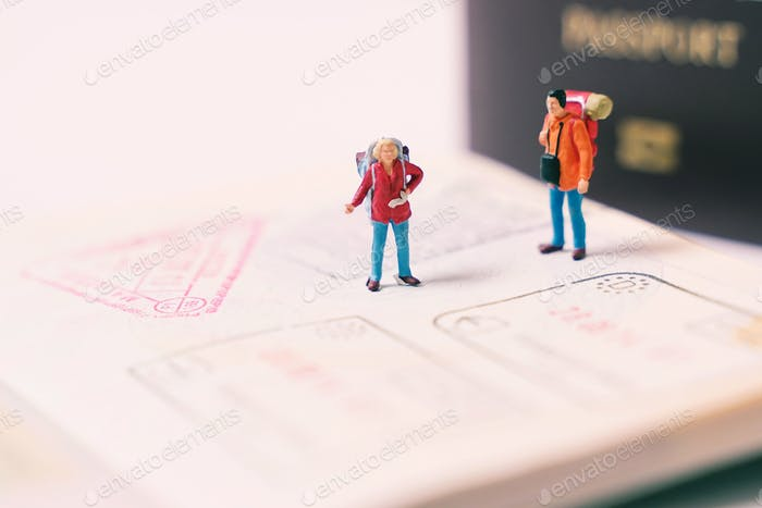 Miniature people figures with backpack walking and standing on passport page with immigration stamps