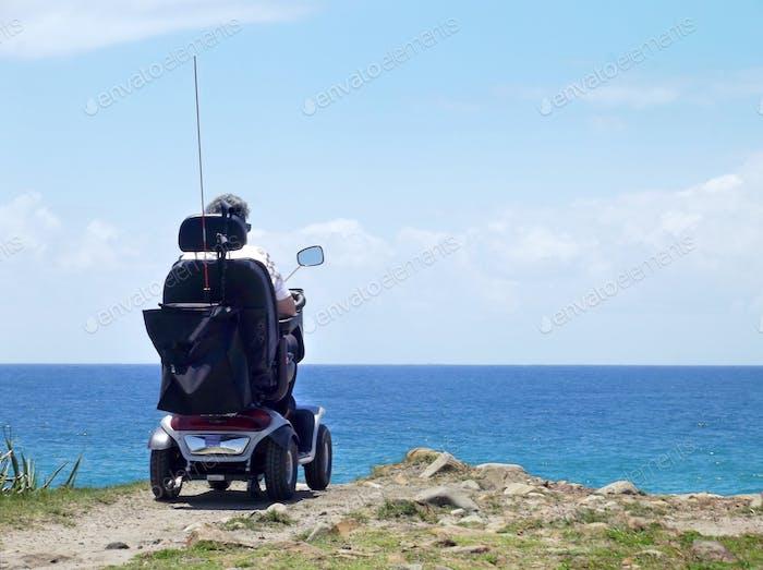 Frau im elektrischen Rollstuhl am Strand