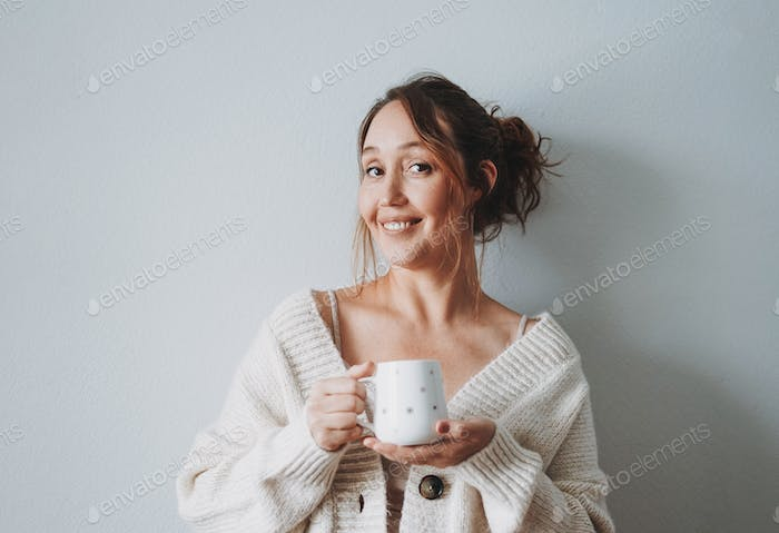 Attractive friendly smiling brunette woman middle age with cup of morning coffee at home cozy vibes