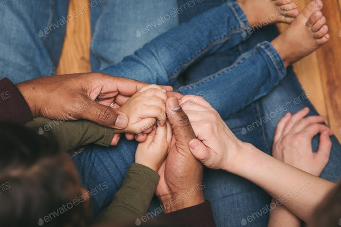 Eine multirassische Familie, die Händchen in Liebe und Unterstützung hält