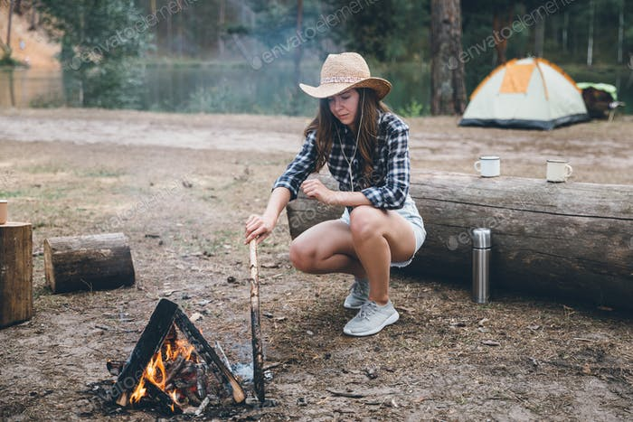 Millennial woman tending to a camp fire while camping and enjoying nature.