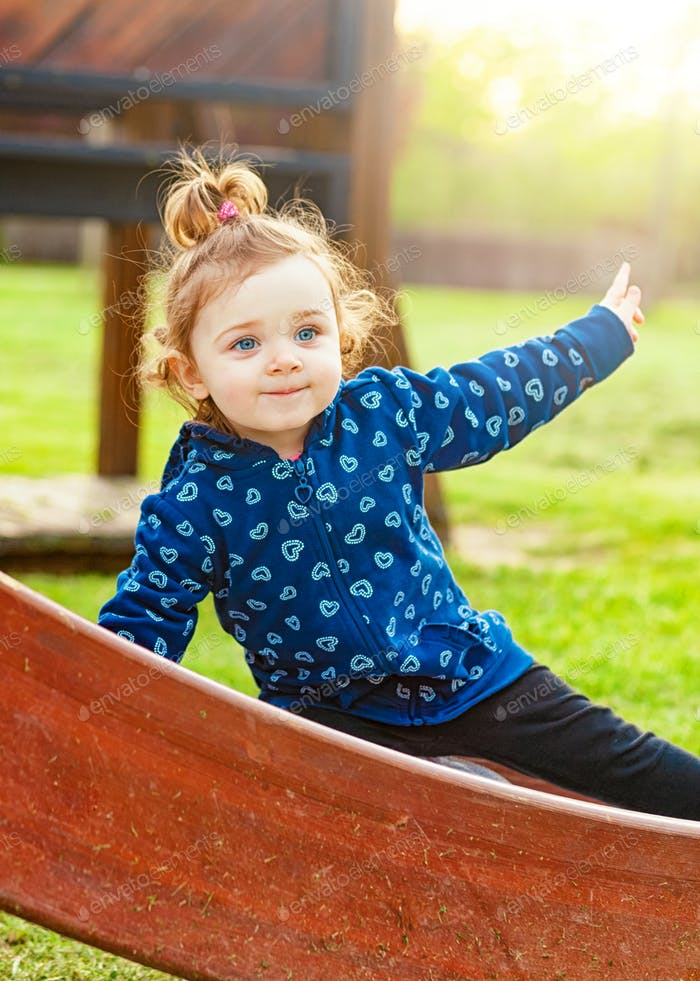 Little baby girl plays happy in the park outdoors in the spring against the backlight.