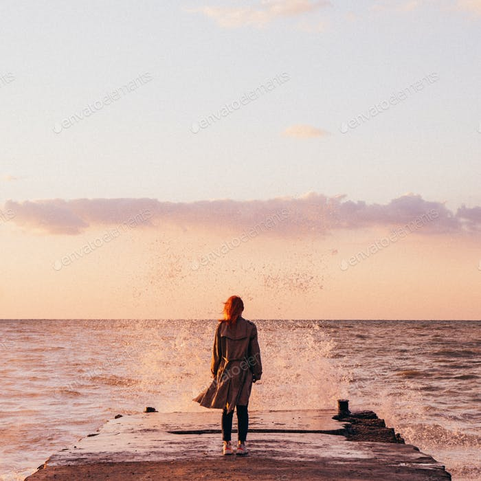 red-haired girl in a cloak of white T-shirt and blue jeans against the sea