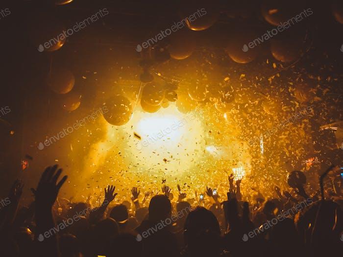 Musikfestival. Nachtleben. Konfetti. Menschenmenge.