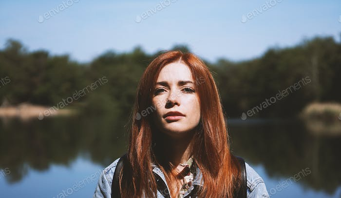 outdoorsy young woman standing by lake