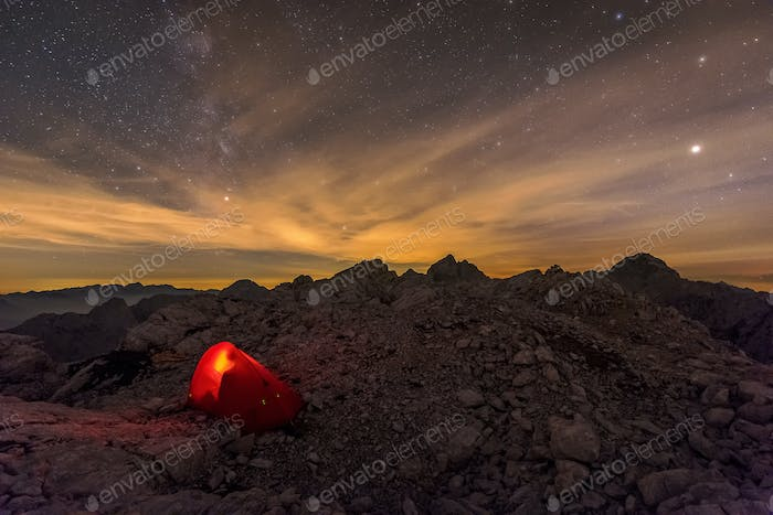 Tent in the mountains under a starry night