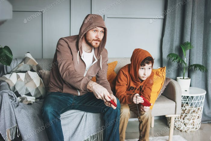 Father and son tween boy in hoodies playing computer games with joystick at home