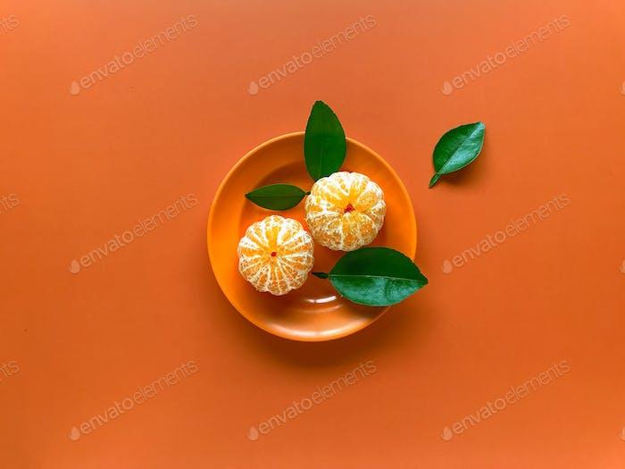 Oranges are in an orange dish on an orange background.