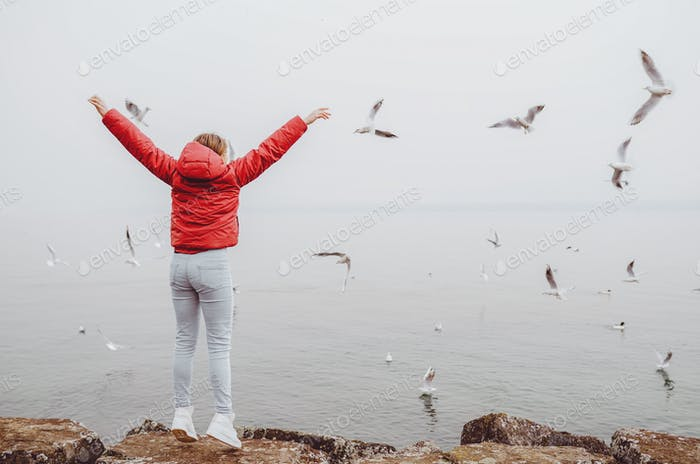 Back view of young teen girl with hands raised up near the sea looking at flying seagulls. Dreams