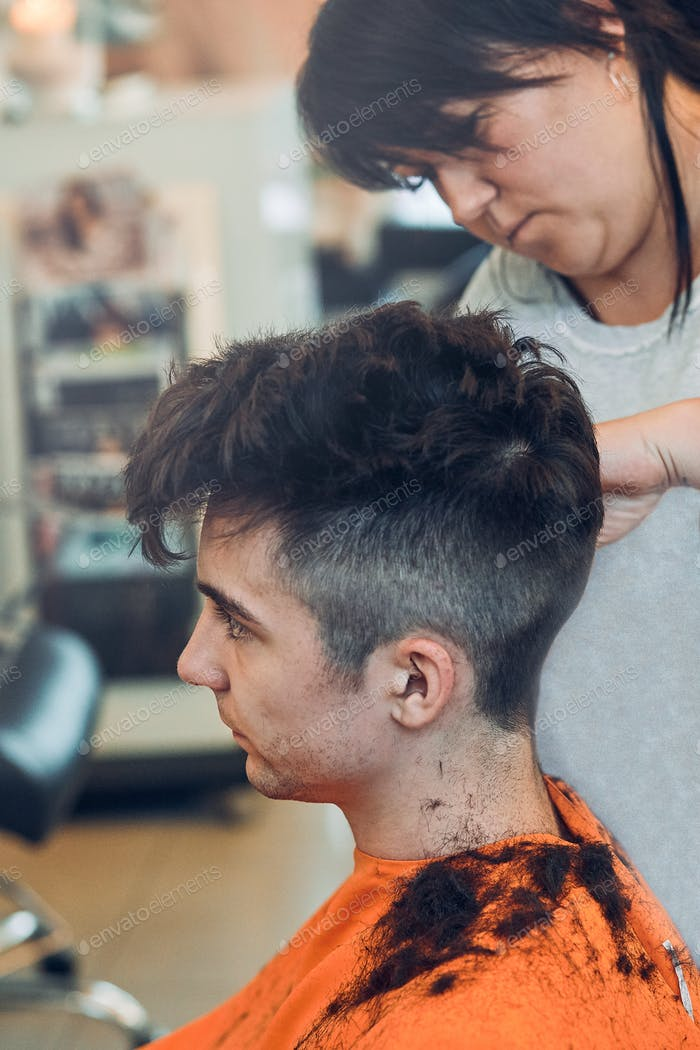 Hairdresser haircutting styling young man