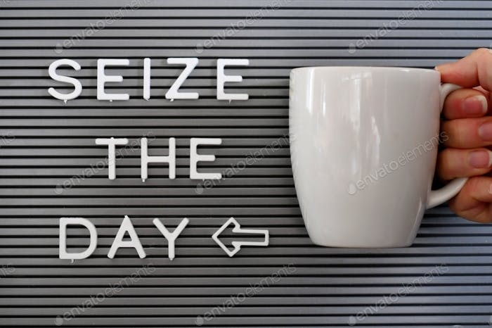 Message board saying Seize the day with a woman holding a coffee mug next to it.