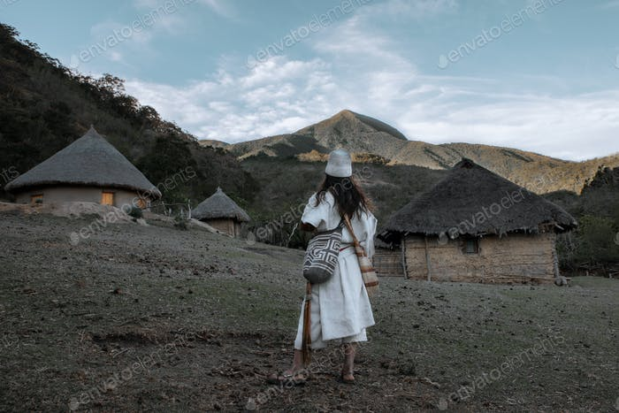 An Arhuaco indigenous man observes the mountain from a local settlement.