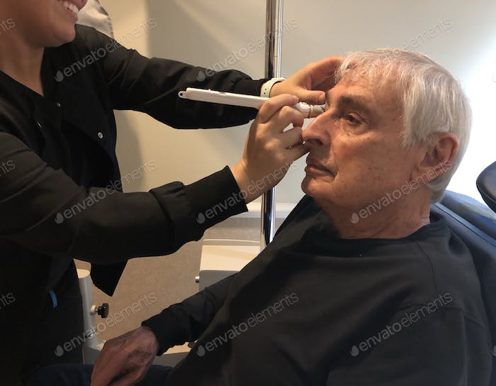 Senior man at eye doctor appointment, being checked for glaucoma and cataracts