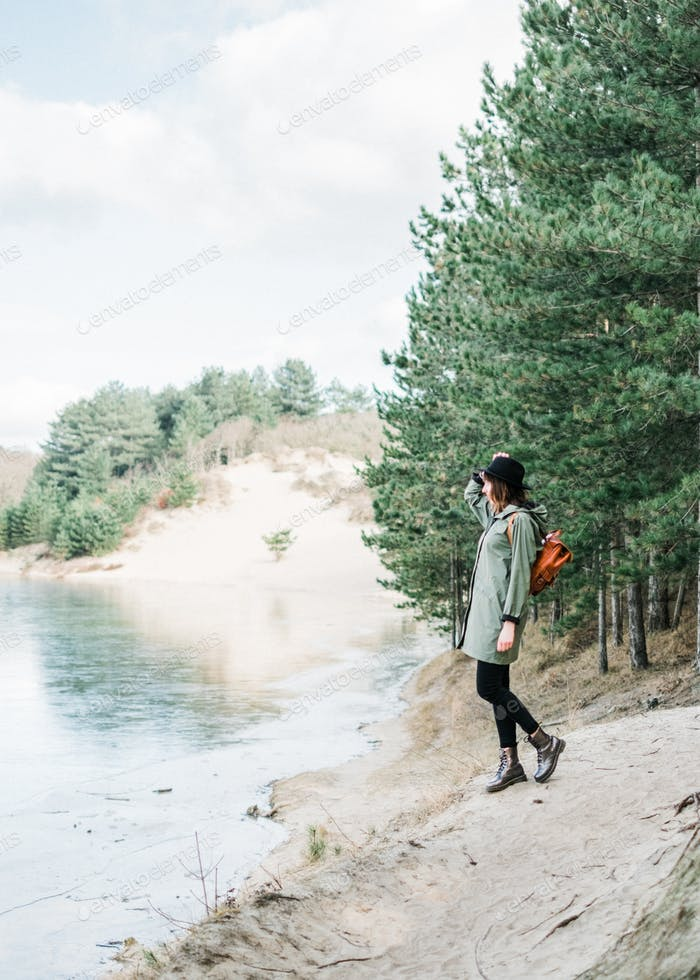 Young woman standing next to a lake, traveling solo wearing a raincoat