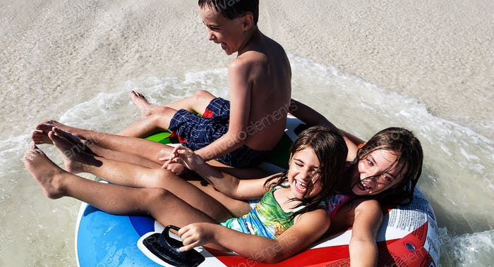 Three kids laugh and have fun on a float in the ocean surf while on vacation...