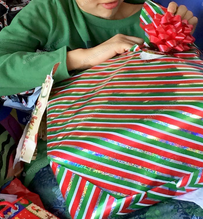 Christmas moments. The happiness of unwrapping a gift on Christmas morning. Gift, Christmas, unwrapp
