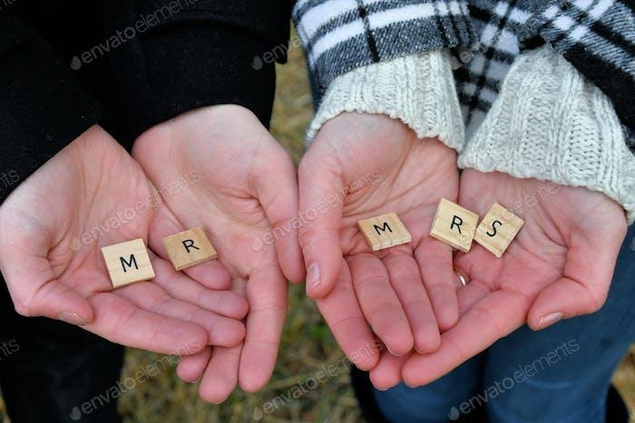 Ein Paar, das die Briefe hält, die Herrn und Frau in ihren Händen buchstabieren