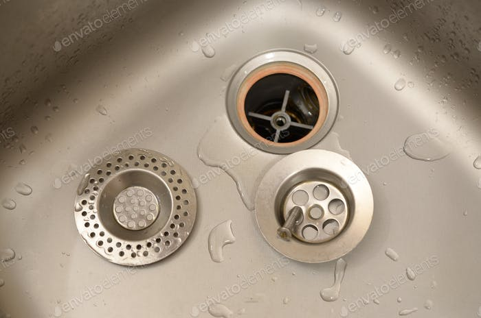 Silvery kitchen sink with a disassembled protective filter. Kitchen sink repair process