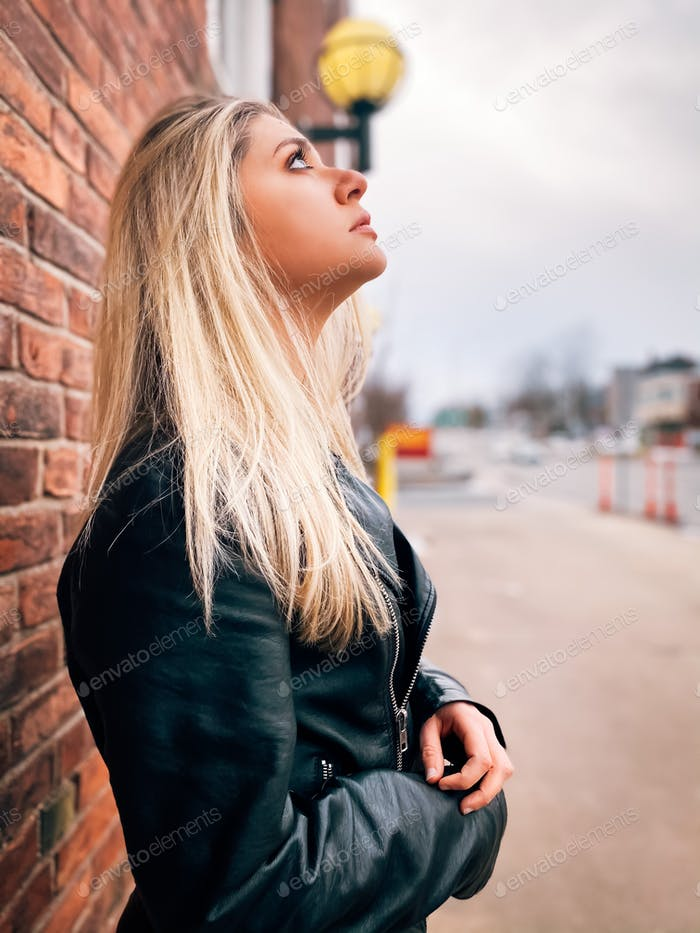 A beautiful blonde woman standing against a brick wall while looking up