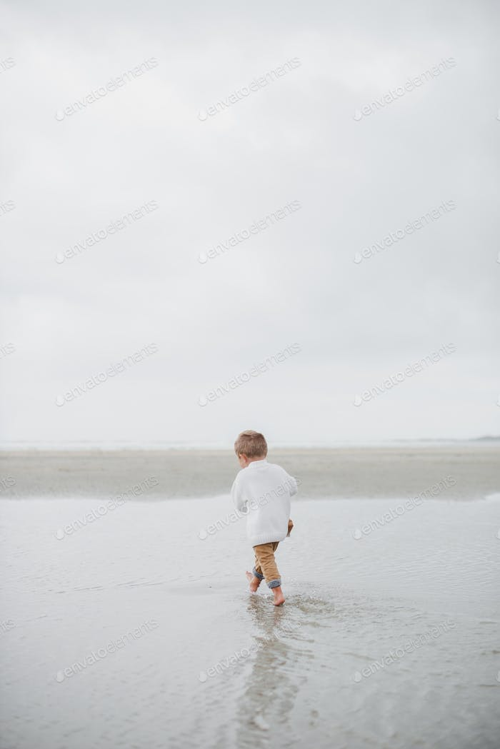 Boy walking on a beach on a grey cloudy day wearing neutral clothes - minimalist lifestyle in