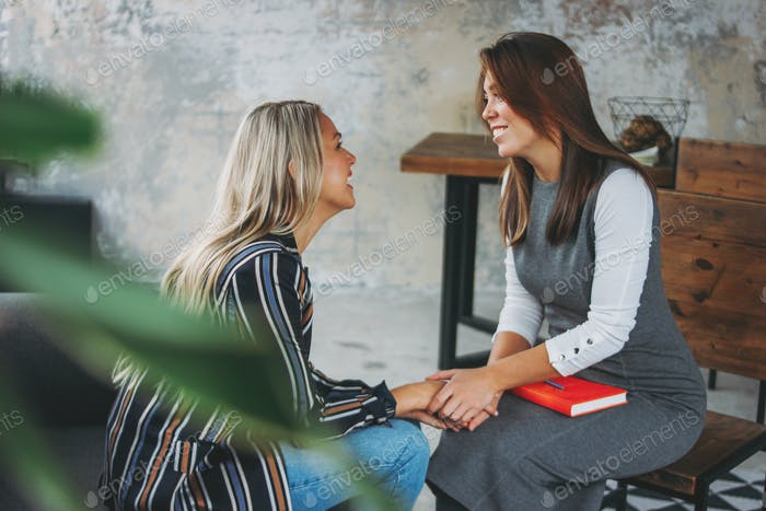 Young successful women colleagues in modern loft office, coaching, mentoring, psychotherapy, therapy