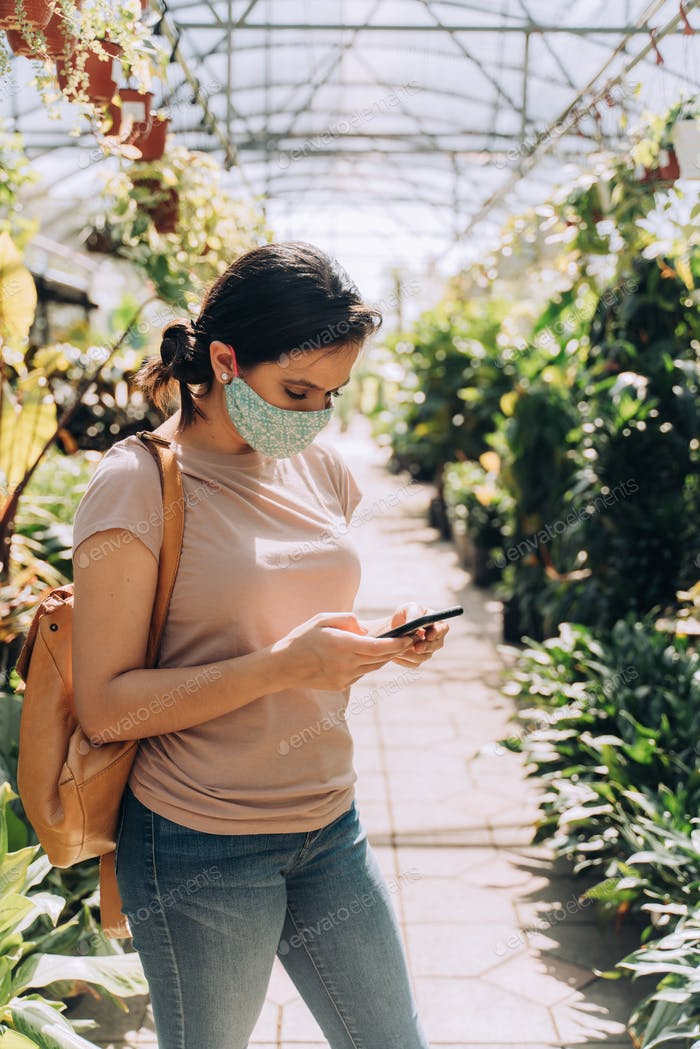 Woman shopping at plant nursery using smartphone during coronavirus pandemic