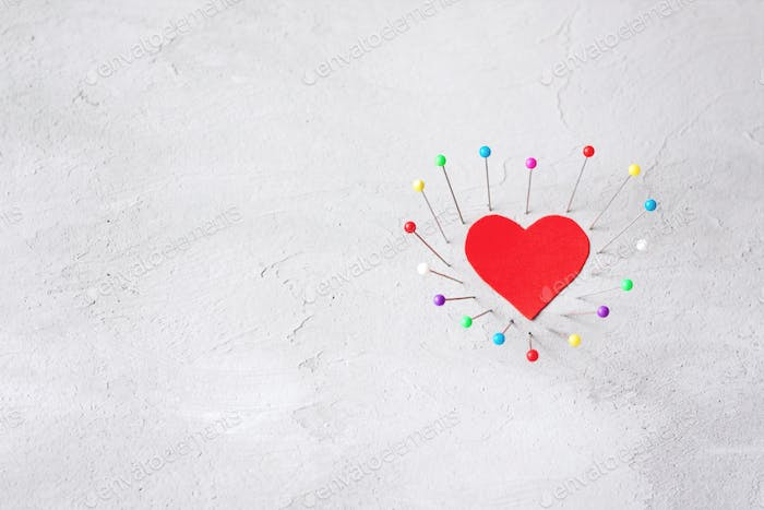 Red paper heart and multicolored sewing pins on gray cement background